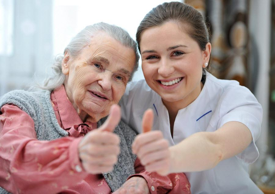 old lady and carer giving thumbs up