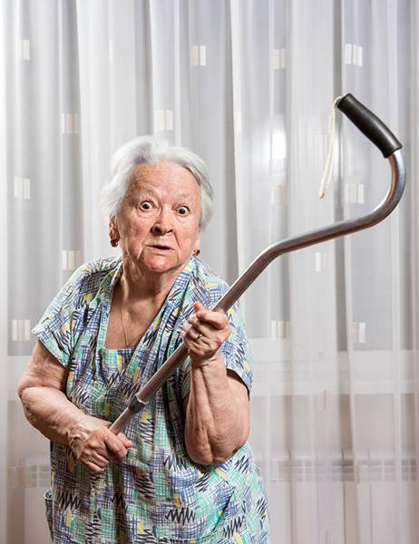 Old angry woman threatening with a cane